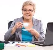 Starsza biznesowa kobieta pije herbaty lub kawy przy biurkiem w biurze, przerwa przy pracą obrazy royalty free