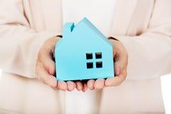 Starsza biznesowa kobieta trzyma błękitnego papieru dom zdjęcia royalty free