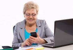 Starsza biznesowa kobieta używa telefon komórkowego i działanie przy jej biurkiem w biurze, biznesowy pojęcie obraz stock