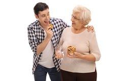 Starsza dama daje ciastkom mężczyzna obraz royalty free