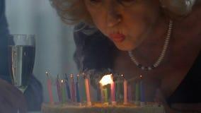 Starsza dama podmuchowa za świeczkach na torcie, odświętność urodziny z mężem zdjęcie wideo