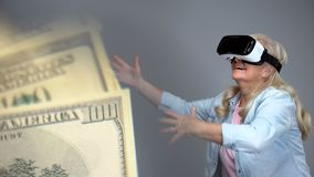 Starsza dama próbuje łapać dolarowych banknoty w VR słuchawki, deponuje pieniądze pojęcie zdjęcie stock