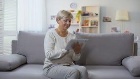 Starsza dama robi zakupy online na pastylce ono uśmiecha się przy kamerą w domu, technologia zbiory