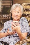 Starsza dama sadzał w domu uczyć się dlaczego używać smartphone obrazy royalty free