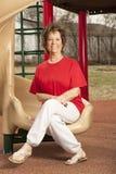 Starsza dama siedzi na obruszeniu Obraz Royalty Free