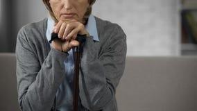 Starsza dama siedzi samotnie na leżance, trzyma ręki na chodzącym kiju, żal zdjęcie royalty free