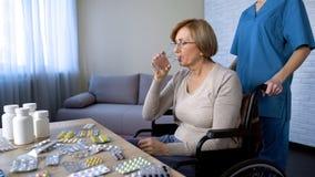 Starsza dama w wózku inwalidzkim przy stołem bierze medycynę, traktowanie w karmiącym domu obraz stock