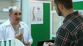 Starsza farmaceuta i młody klient dyskutuje lekarstwa Fotografia Royalty Free