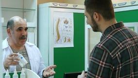 Starsza farmaceuta opowiada męski klient podczas gdy brać medycynę półka Obrazy Royalty Free