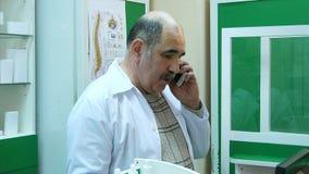 Starsza farmaceuta opowiada na telefonie komórkowym podczas gdy sprawdzać receptę w aptece Zdjęcia Stock