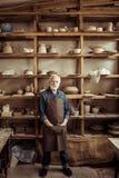 Starsza garncarka w fartuch pozyci przeciw półkom z ceramicznymi towarami przy warsztatem obrazy royalty free