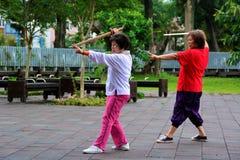 Starsza kobieta ćwiczy tai chi z kordzikami zdjęcie royalty free