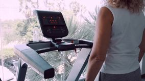 Starsza kobieta angażuje na karuzeli w gym przeciw tłu panoramiczny okno zdjęcie wideo