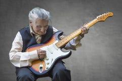 Starsza kobieta bawić się gitarę Zdjęcie Stock