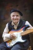 Starsza kobieta bawić się gitarę Zdjęcie Royalty Free