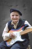 Starsza kobieta bawić się gitarę Obrazy Royalty Free