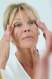 Starsza kobieta bierze opiekę jej skóra zdjęcia royalty free