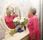 Starsza kobieta blisko odzwierciedla Zdjęcie Stock