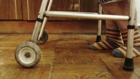 Starsza kobieta chodzi wolno w domu za pomocą zbiory