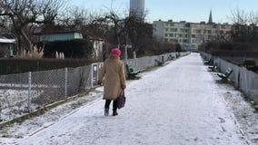 Starsza kobieta chodzi wzdłuż ścieżki w przydziałach zbiory wideo