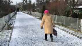 Starsza kobieta chodzi wzdłuż ścieżki w przydziałach zbiory