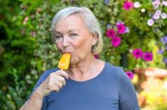 Starsza kobieta cieszy się odświeżającego lukrowego lolly Zdjęcia Stock
