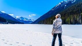 Starsza kobieta cieszy się widok zamarznięty Duffey Jeziorny iin Kanada BC obrazy royalty free