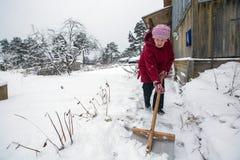 Starsza kobieta czyści śnieżnego pobliskiego dom Pomoc Obrazy Stock