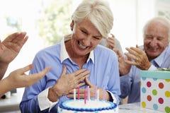 Starsza kobieta Dmucha Out Urodzinowego torta świeczki Przy rodziny przyjęciem fotografia stock