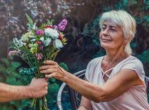 Starsza kobieta dostaje pięknego bukiet śródpolni kwiaty Fotografia Royalty Free