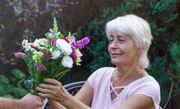 Starsza kobieta dostaje pięknego bukiet śródpolni kwiaty Obraz Stock