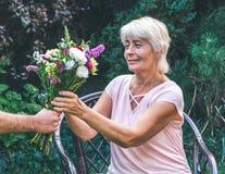 Starsza kobieta dostaje pięknego bukiet śródpolni kwiaty Zdjęcia Stock