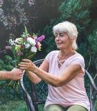 Starsza kobieta dostaje pięknego bukiet śródpolni kwiaty Obraz Royalty Free
