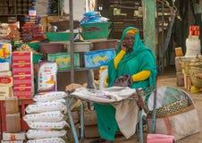 Starsza kobieta dzwoni jej telefon komórkowego w zielonym Abaya przy sprzedaży budka w rynku Dongola zdjęcia stock