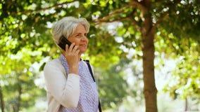 Starsza kobieta dzwoni na smartphone w parku zbiory
