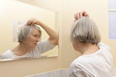 Starsza kobieta egzamininuje włosianą stratę zdjęcia royalty free