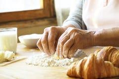 Starsza kobieta gotuje francuskich croissants, nagie marszczyć ręki, składniki, miękka część ranku ciepły światło, odgórny widok Fotografia Stock