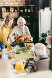 starsza kobieta i jej córki przewożenia indyk dla dziękczynienie gościa restauracji z ich zdjęcia stock