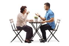 Starsza kobieta i młodego człowieka gawędzenie pić kawa i zdjęcie stock