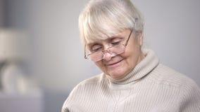 Starsza kobieta jest ubranym eyeglasses i czytanie, wzrok problemy, opieka zdrowotna obraz royalty free