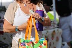 Starsza kobieta jest ubranym rodowitego amerykanina - boho jewlery z jaskrawym torba na zakupy, bidon i trzymać USD rachunki przy obrazy stock