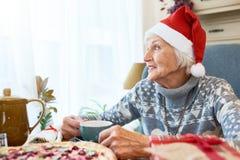 Starsza kobieta Jest ubranym Santa kapelusz przy Obiadowym stołem fotografia stock