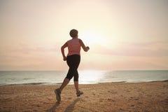 Starsza kobieta jogging na morze plaży Obraz Royalty Free
