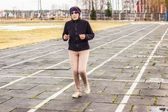 Starsza kobieta jogging przy stadium fotografia royalty free