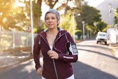 Starsza kobieta jogging w ulicie obrazy stock