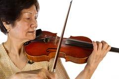 Starsza kobieta koncentruje podczas gdy bawić się skrzypce Fotografia Royalty Free