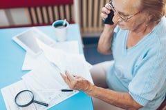 Starsza kobieta kontaktuje się custumer usługuje po otrzymywać rachunek obraz stock