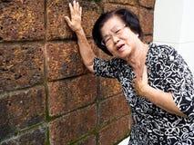 Starsza kobieta ma klatka piersiowa ból i jej mienie pierś przez kierowego infarction Ataka Serca pojęcie Zdjęcie Royalty Free