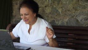 Starsza kobieta macha szczęśliwie laptopem zdjęcie wideo