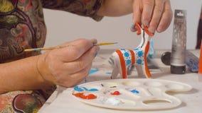 Starsza kobieta maluje rogacza zbiory